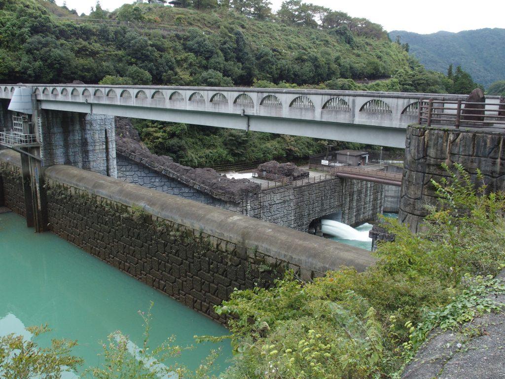 石小屋ダムの堤体越しに愛川第2発電所の放流