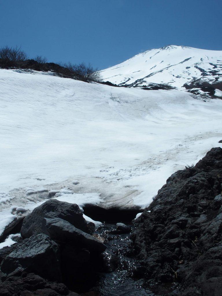大きな雪渓の下をくぐり抜けて